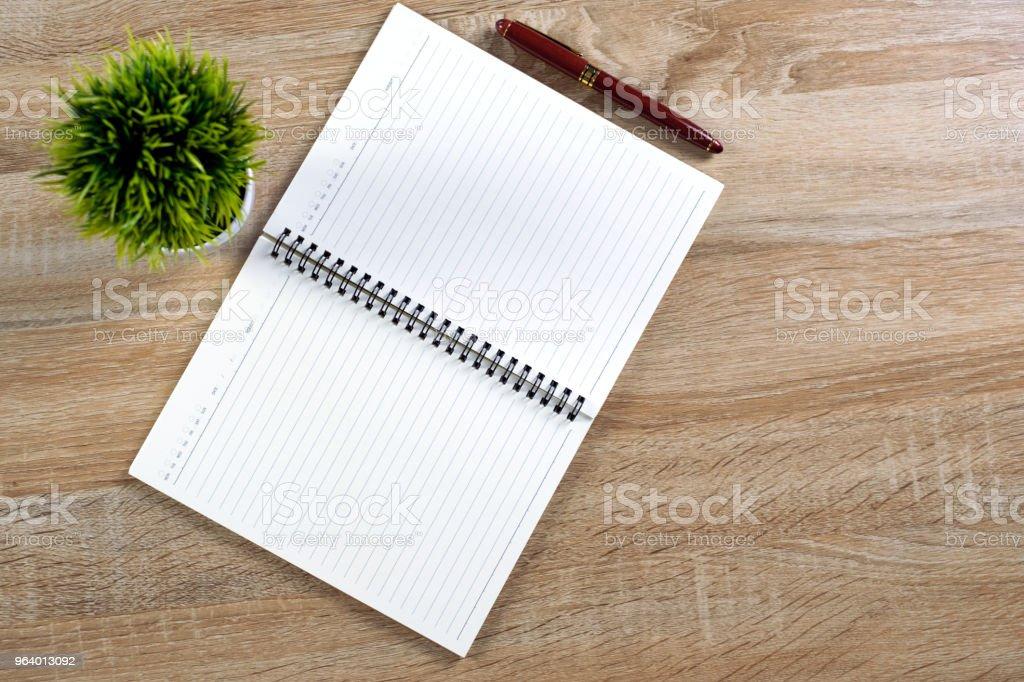 万年筆やノートと白い花瓶をコピー スペース、オフィス デスク コンセプト木製作業テーブルの上に小さなデコレーション ツリー インク ペン。平面図です。 - インクのロイヤリティフリーストックフォト