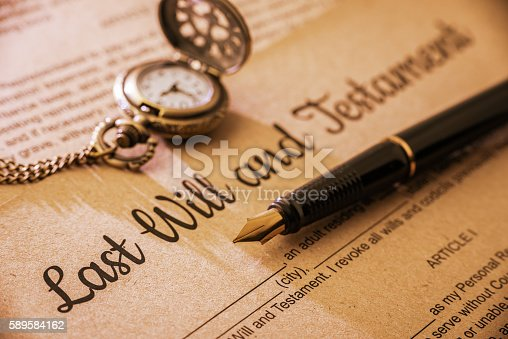 584597964 istock photo Fountain pen, pocket watch on a last will and testament. 589584162