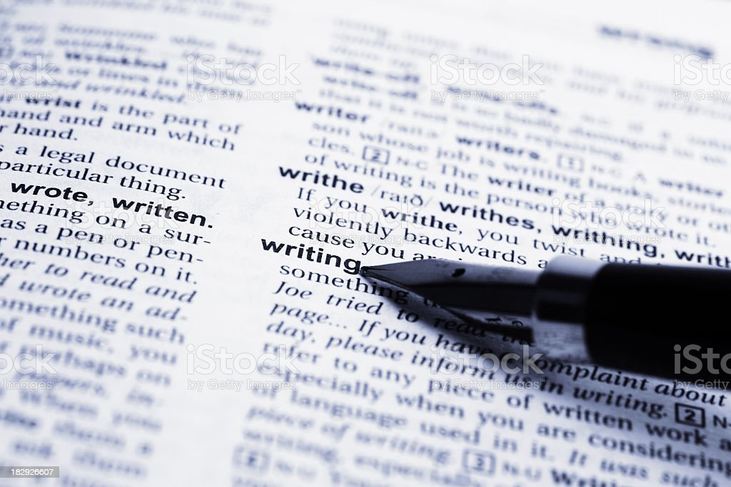 Fountain pen pointing to the word writing in a dictionary royalty-free stock photo