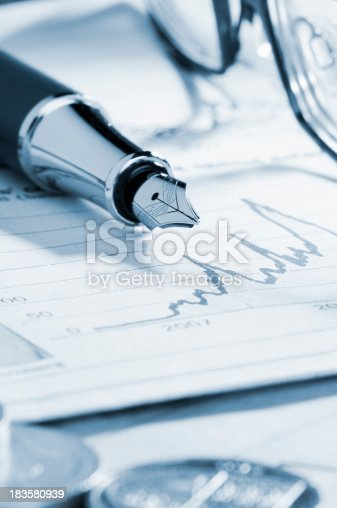 A silver fountain pen on a newspaper. There are some coins in the foreground and a pair of reading glasses to the side. The pen is lying on a business performance graph in the newspaper. The focus is selectively on the end of the pen and the performance graph.