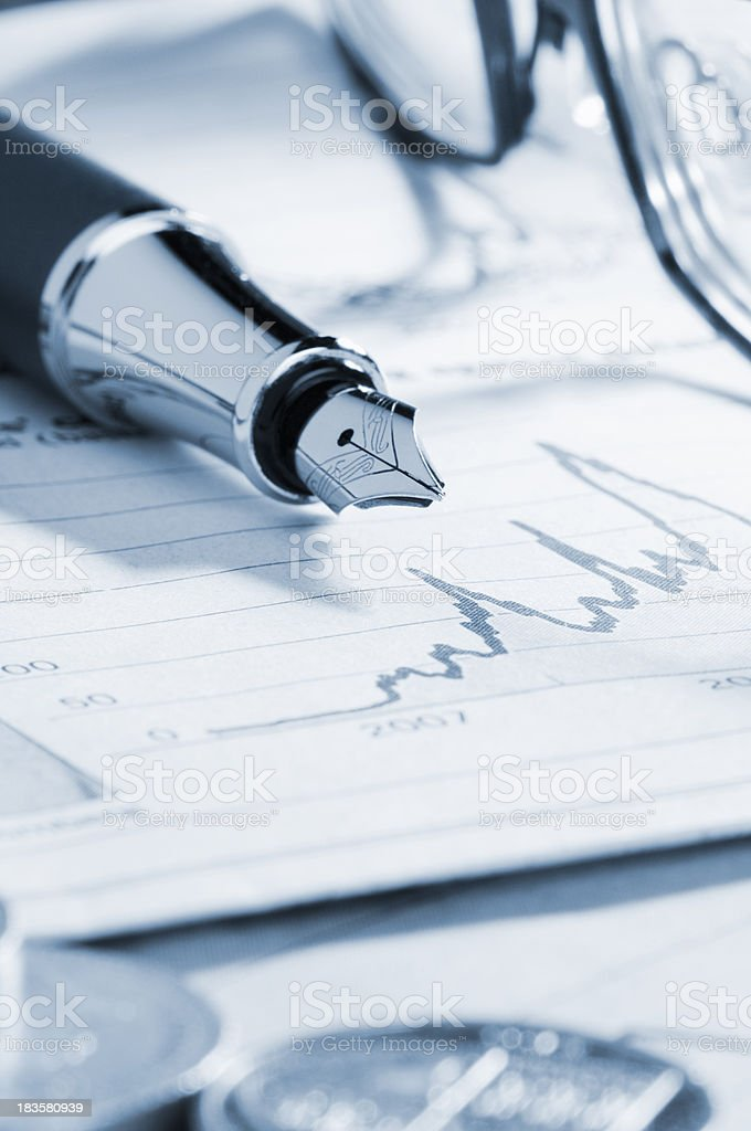 Fountain pen resting on a business analysis stock photo