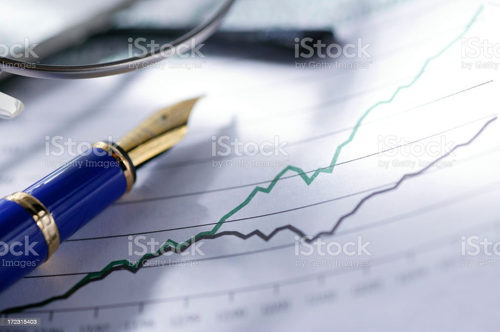 Fountain pen resting on growth chart stock photo
