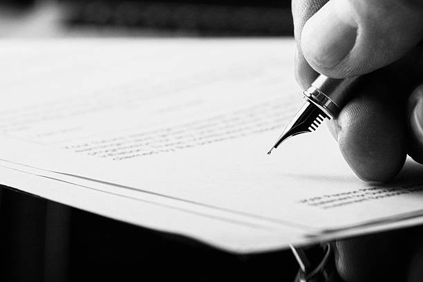 Fountain Pen Signature. A hand holding a fountain pen and about to sign a letter. Styling and small amount of grain applied. bank statement stock pictures, royalty-free photos & images