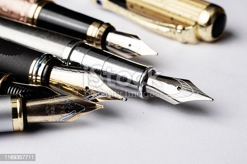 Five fountain pens in a row on white paper