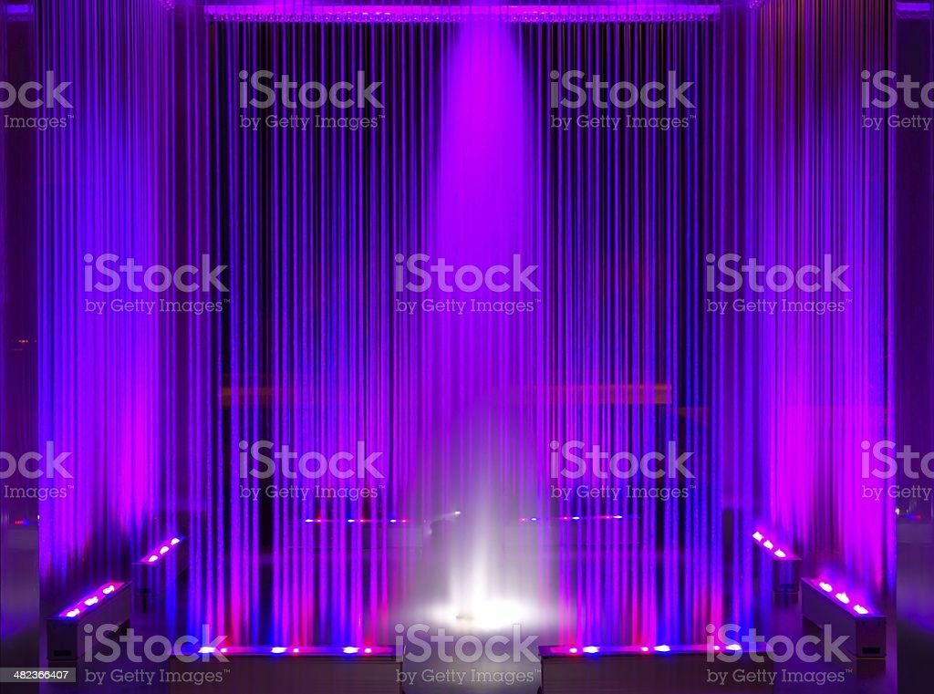 Fountain, violet illuminated flowing water by night, abstract as background royalty-free stock photo
