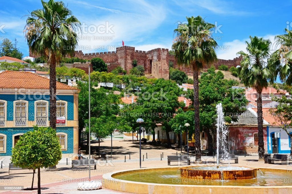 Fountain with castle to the rear, Silves, Portugal. stock photo