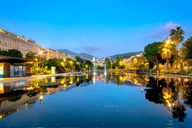 Fuente con espejo reflejo de la ciudad de noche en la Plaza Massena en Niza. Francia - foto de stock
