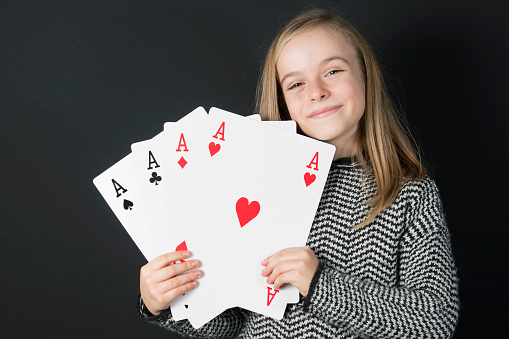 A smart blonde little girl (10 Y old) is holding in her hands four cards, they are aces. The cards are in a giant size. Black background.