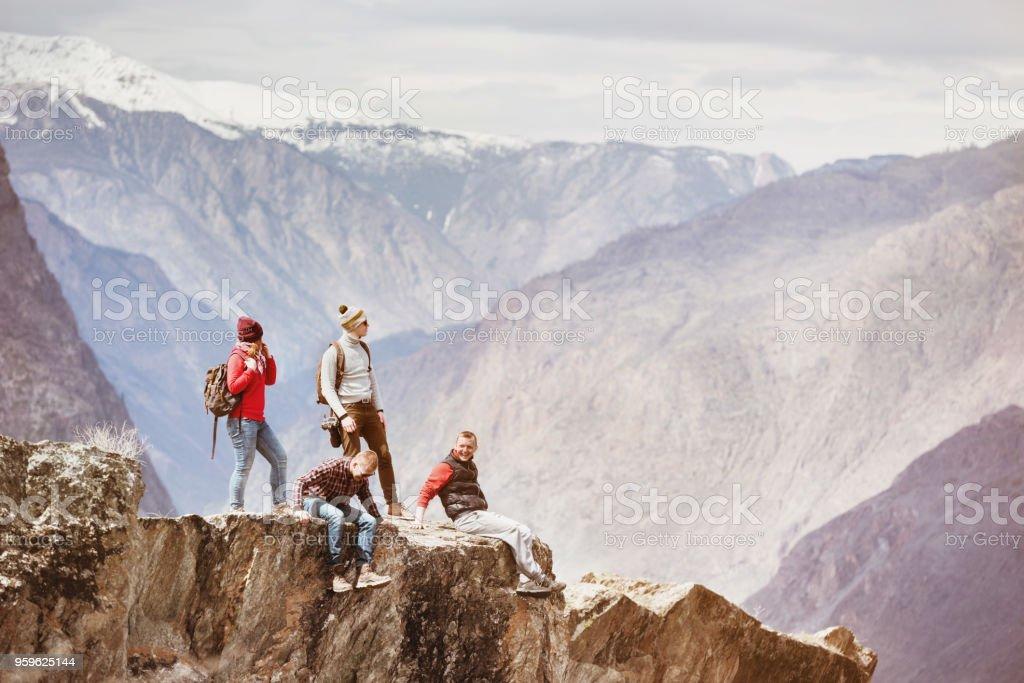 Cuatro amigos activos en acantilado de la montaña - Foto de stock de Acantilado libre de derechos
