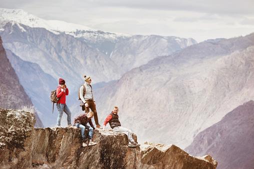 Cuatro Amigos Activos En Acantilado De La Montaña Foto de stock y más banco de imágenes de Acantilado