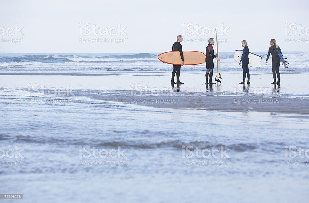 Quatro adultos na praia com pranchas de surf, boogie uma foto de stock royalty-free
