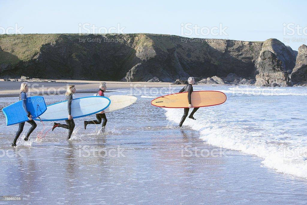 Quatro adultos com pranchas de surfe correndo na água - foto de acervo