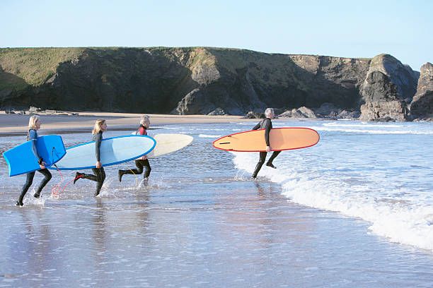 Four adults with surfboards running into the water stock photo