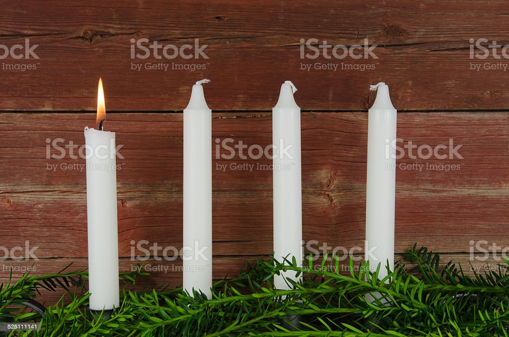 Four advent candles at an old plank wall stock photo