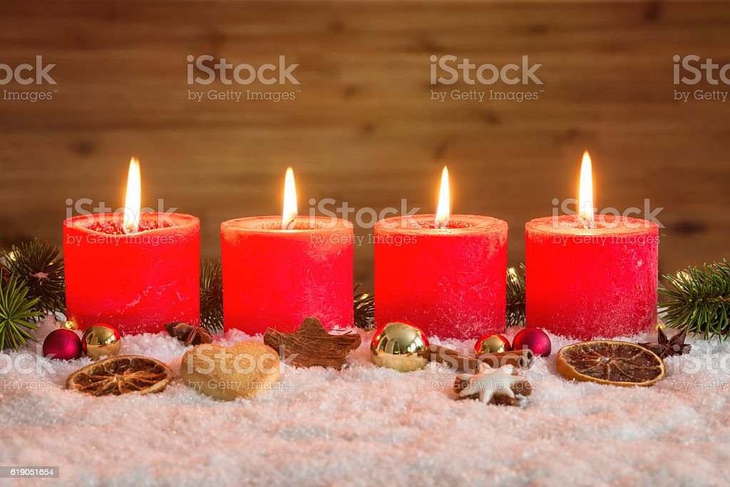 Four advent candles lit in snow stock photo