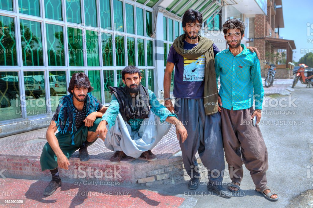 Four Afghans outside the Iranian city. stock photo