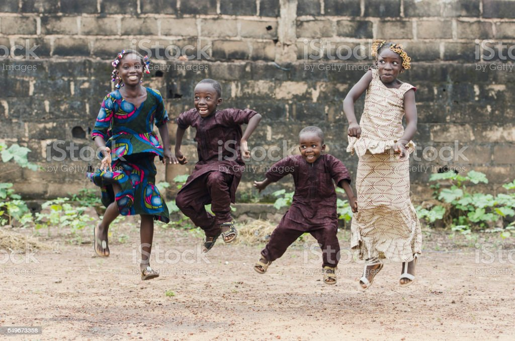 Four African children jumping as high as possible playing outdoors stock photo