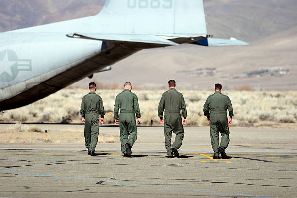 Four air force pilots walking away from the camera Four enlisted Marines walking confidently back to their C-130.   flight suit stock pictures, royalty-free photos & images