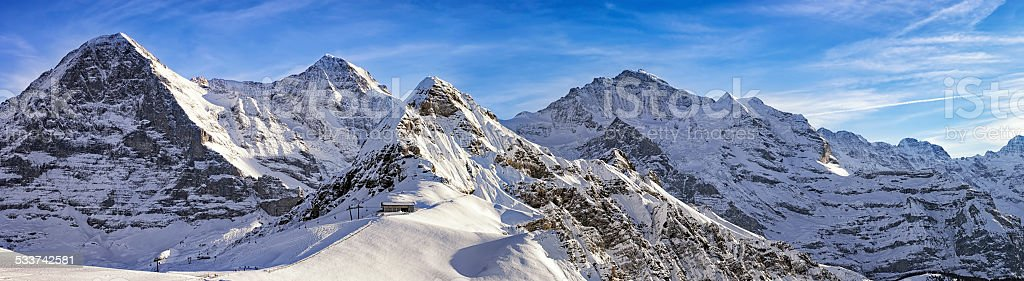 Four alpine peaks and skiing resort in swiss alps stock photo