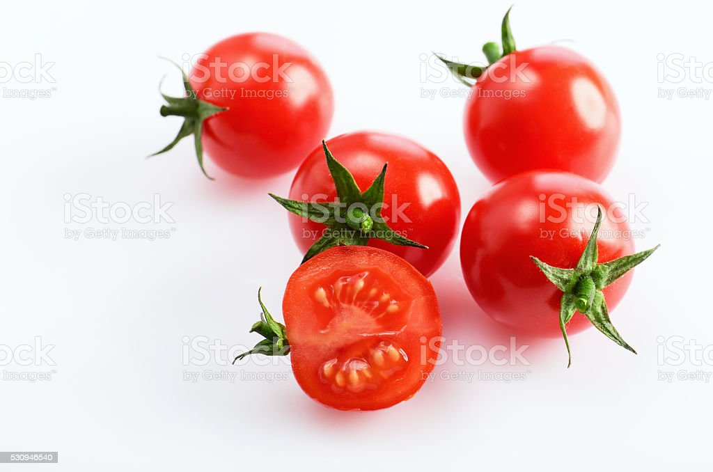 four and a half cherry tomatoes on the white background stock photo