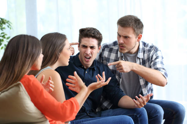 Four angry friends arguing at home stock photo