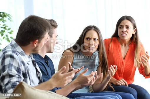 istock Four angry friends fighting at home 1148871462