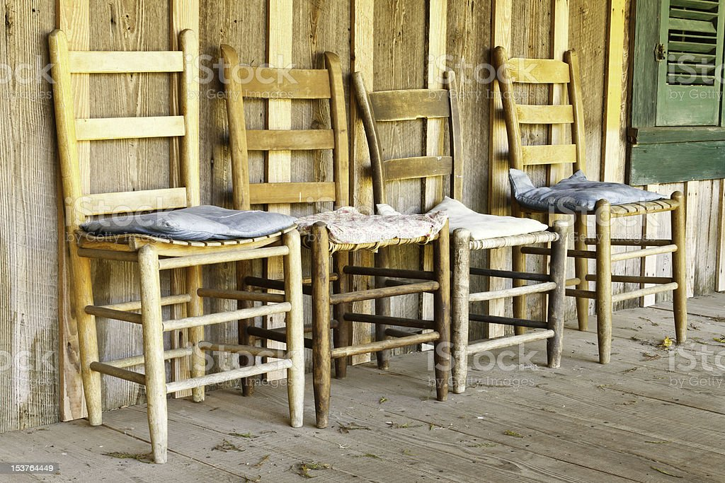 Four Antique Chairs On Porch Of Wood Farmhouse royalty-free stock photo