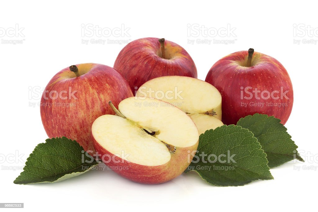 Four apples with one cut in half over white background stock photo