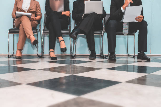 vier bewerber sitzen auf stühlen und bewerbungsgespräch vorbereiten. - outfit vorstellungsgespräch stock-fotos und bilder