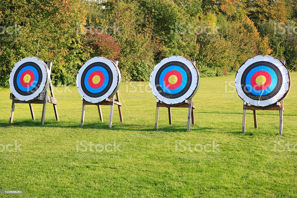 four archery targets in a row on green meadow stock photo