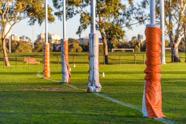 Four Australian football goal posts wrapped with protective padding in a football oval at Carlton, Melbourne, Australia stock photo