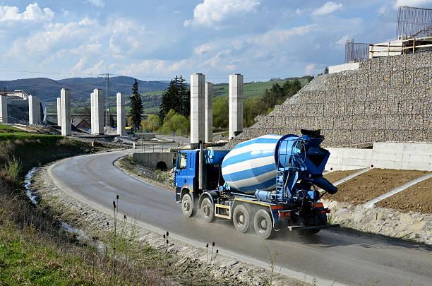 Cuatro ejes camión mezcladora cerca de la autopista en construcción - foto de stock