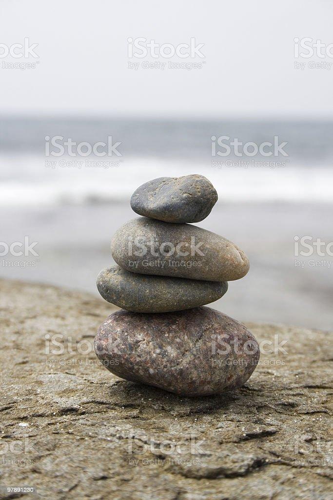 four balanced stones on a rocky beach royalty-free stock photo