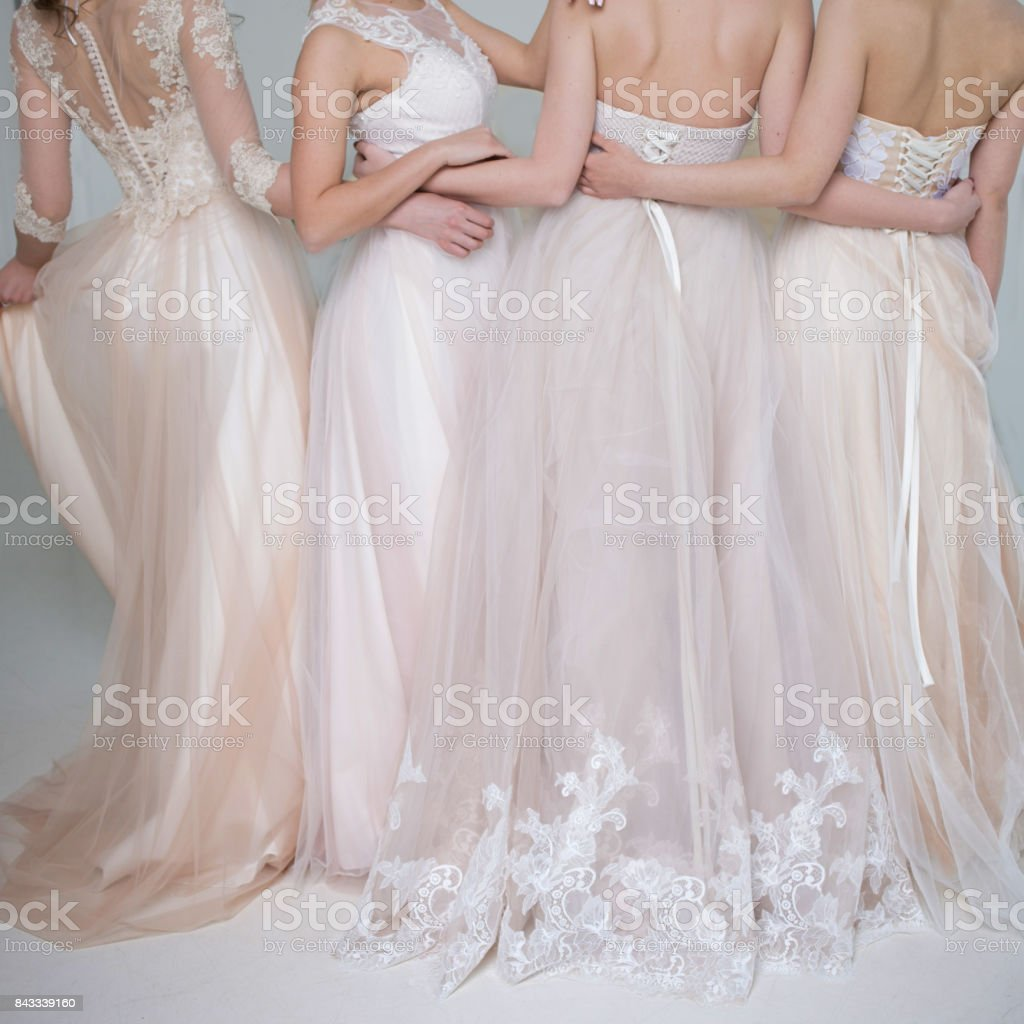 Four beautiful bridesmaid dresses in pastel colors are in each other's arms. Back, close-up lace skirts stock photo
