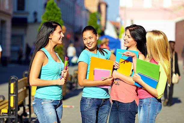 four beautiful college girls talking on the street four beautiful college girls talking on the street college fair stock pictures, royalty-free photos & images