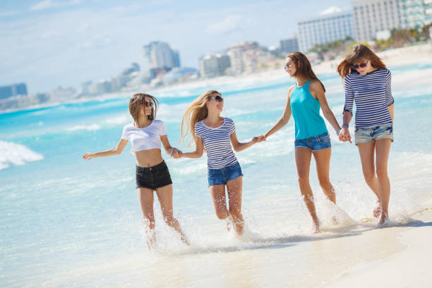 Four beautiful women spend time on the beach, at a wonderful resort in Mexico stock photo