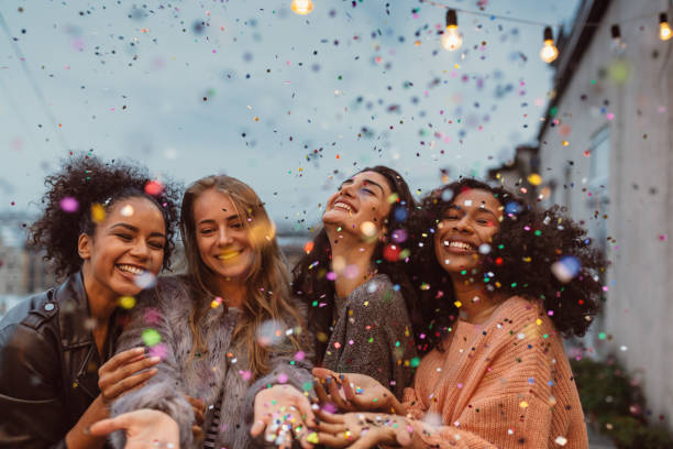 Four beautiful women standing at a terrace under confetti. stock photo