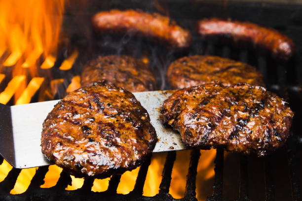 Four Beef Burgers and Two Bratwursts on a hot Barbeque Grill stock photo