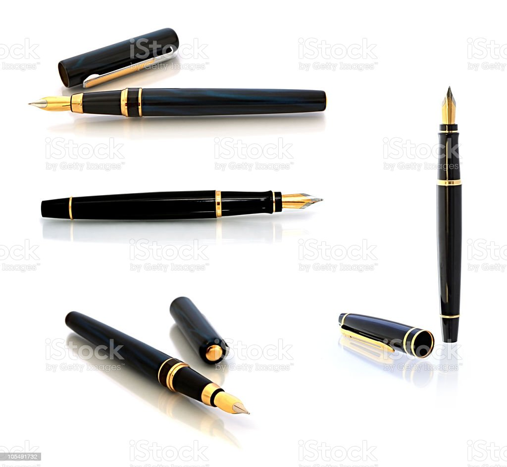 Four black and gold fountain pens in various poses stock photo