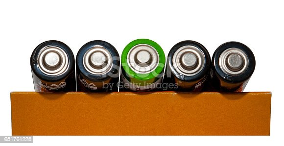 istock Four black battery type AAA, battery one green, top view, white background, isolated 651761228