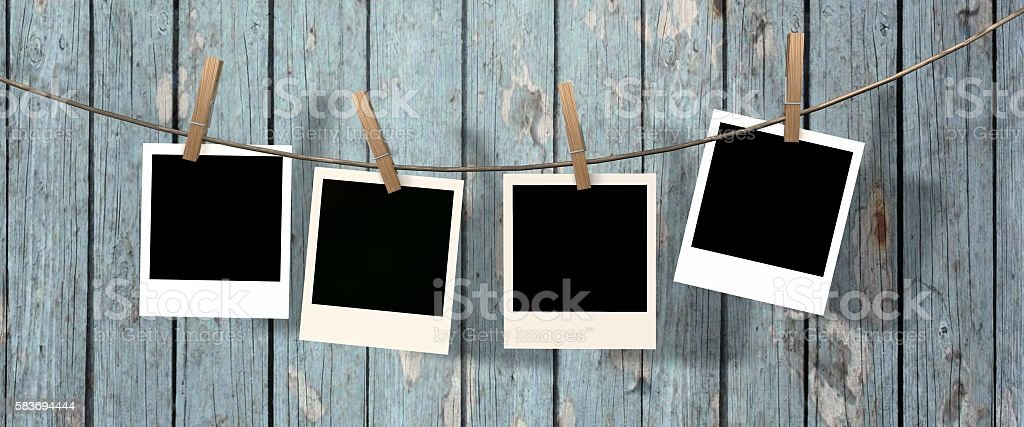 four blank instant photos hanging on the clothesline stock photo