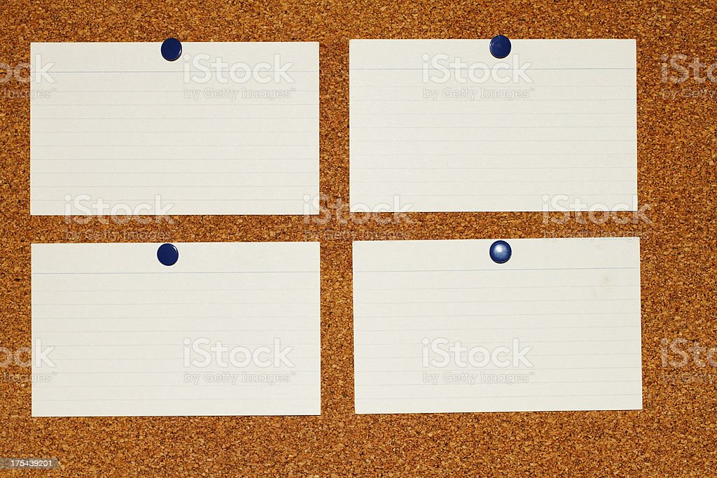 Four blank old index cards pinned to cork noticeboard stock photo