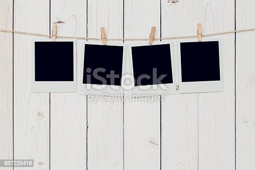 istock Four blank photo frame hanging on white wood background 637233416