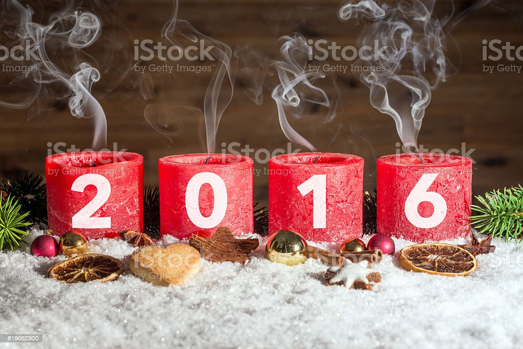 Four blown out advent candles with 2016 in snow stock photo
