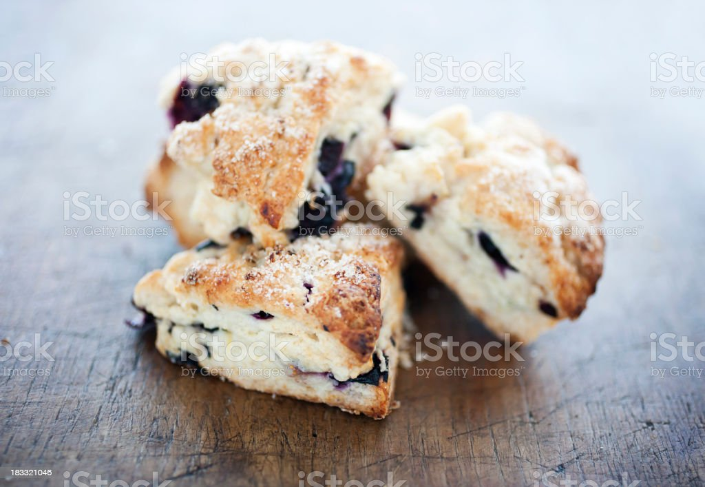 Four Blueberry scone pastries on a wooden table royalty-free stock photo