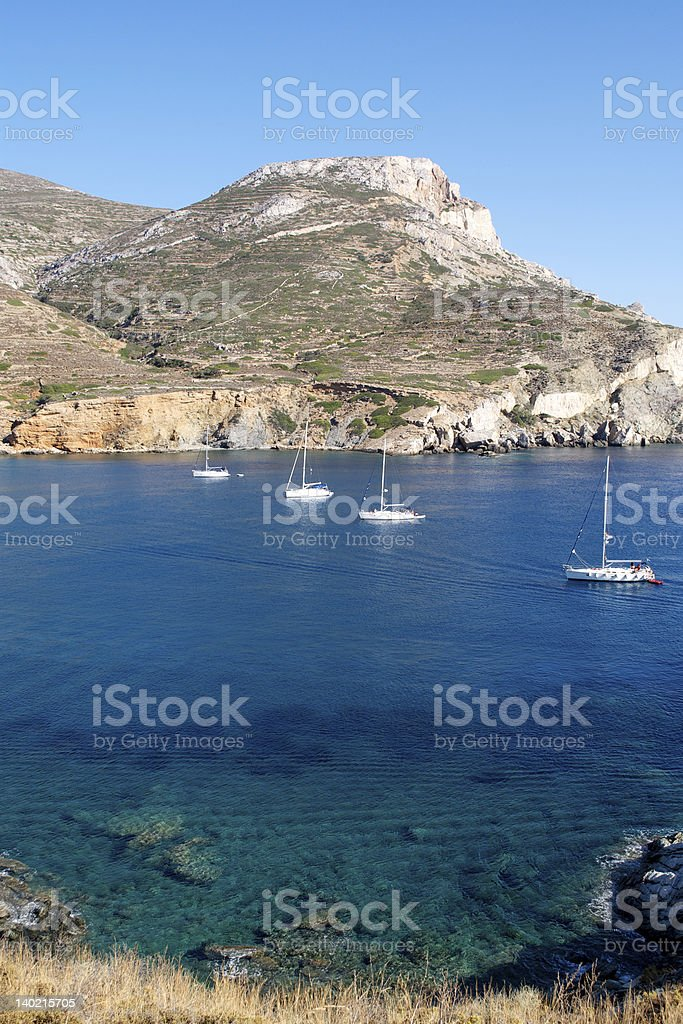 Four boat in a beautiful bay, Folegandros, Greece stock photo