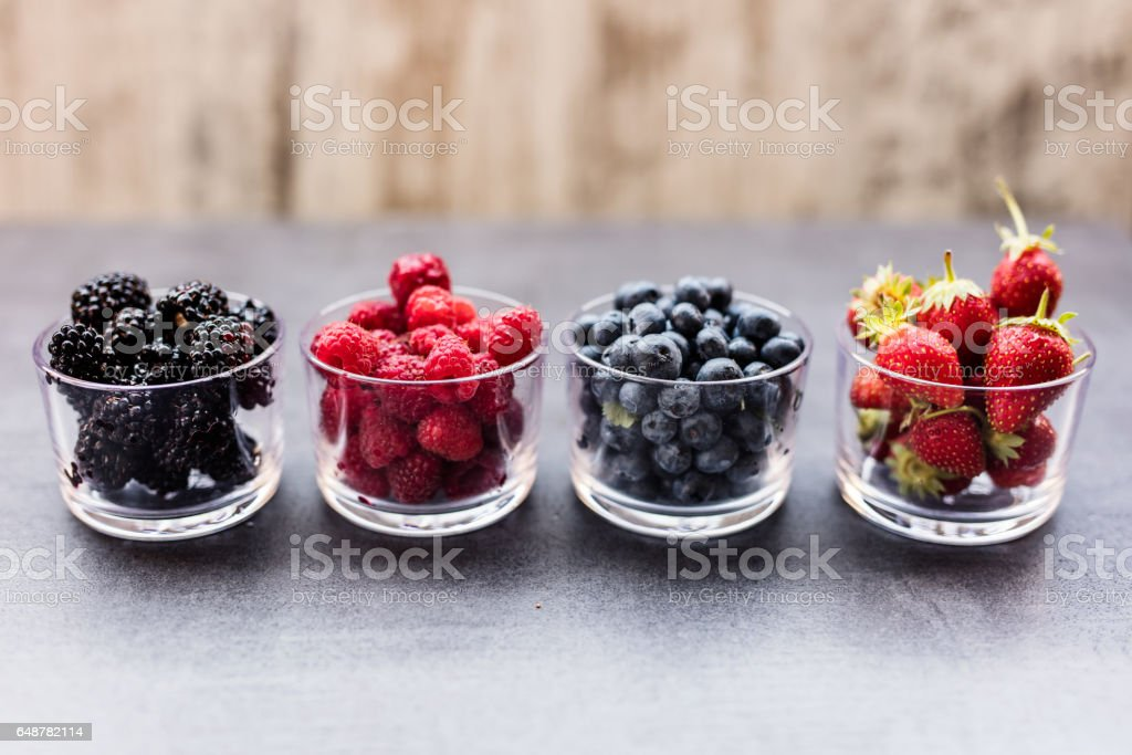 A four bowls overflowing with summer berries like strawberries, raspberries, blueberries and blackberries. stock photo