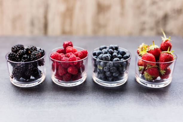 a four bowls overflowing with summer berries like strawberries, raspberries, blueberries and blackberries. - berry stock photos and pictures