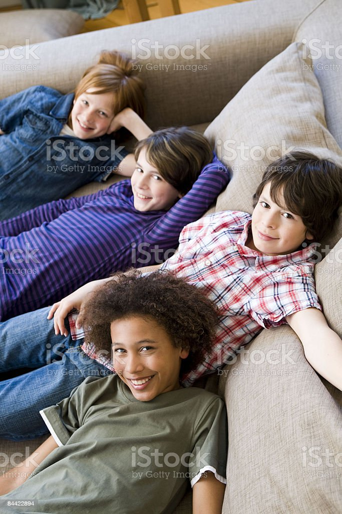 Four boys hanging round on a couch royalty-free stock photo