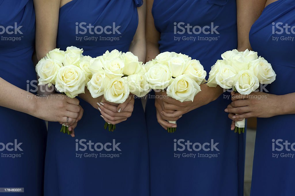 four bridesmaids holding white rose wedding bouquets stock photo